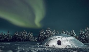 Exotic night in a snow igloo during winter under the frozen night with aurora borealis of Finnish Lapland