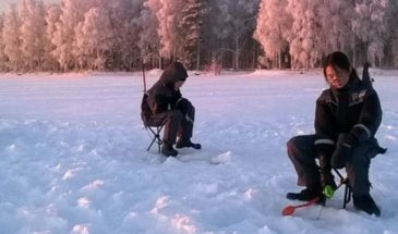 ICE FISHING ON THE FROZEN LAKE OR RIVER rovaniemi lapland