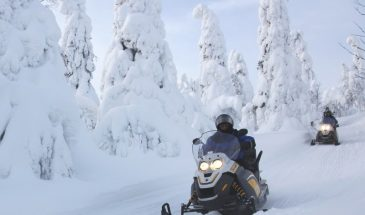 Snowmobile safari in kuusamo russia border finland in the winter snowy forest