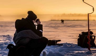Ice fishing on a frozen lake Beyond Arctic Rovaniemi Lapland