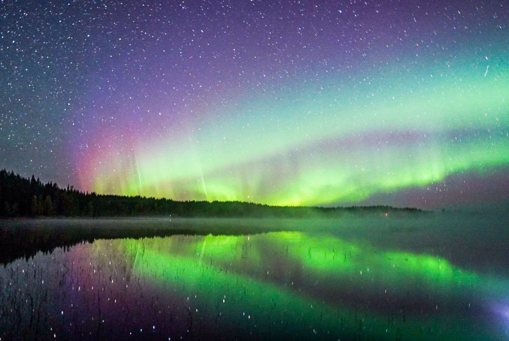 Showing the reflection of the Northern lights in a lake